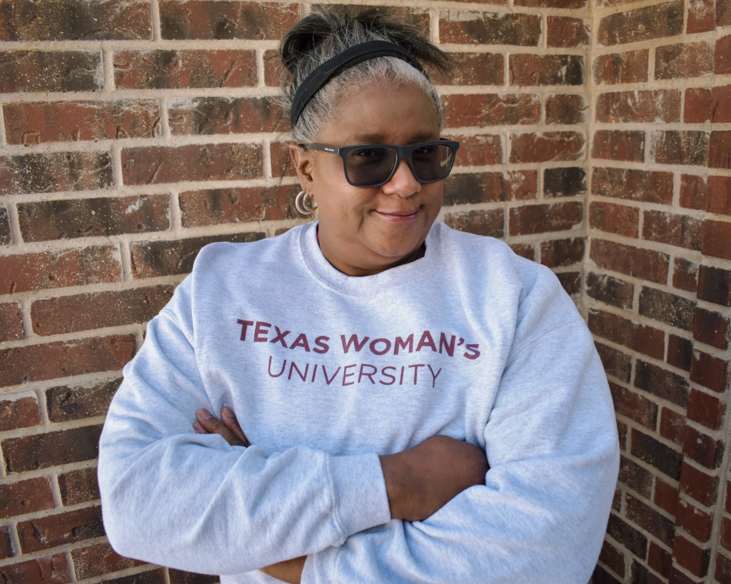 Vicki Byrd stands with her arms crossed and a wise smile on her face in front of some red brick while wearing a light gray sweater with the words Texas Woman's University in maroon